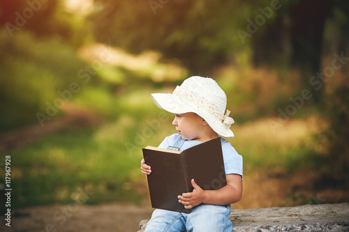 little girl with book in the Park at sunset