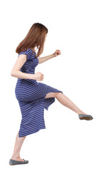 skinny woman funny fights waving his arms and legs. Isolated over white background. The brunette in a blue striped dress beat someone down.