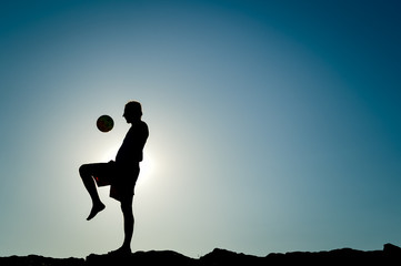 Male silhouette at dawn, player kicking ball, sunny blue sky background outdoors