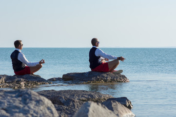 Two businessmen meditating on the beach