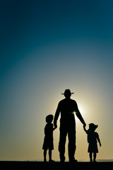 Beautiful sunset silhouette of father with kids, outdoors background