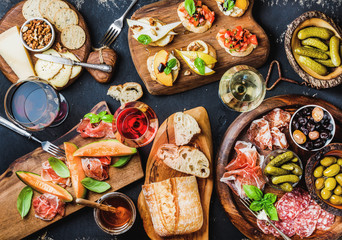 Italian antipasti wine snacks set. Brushettas, cheese variety, Mediterranean olives, pickles, Prosciutto di Parma with melon, salami and wine in glasses over black grunge background, top view Fotomurales