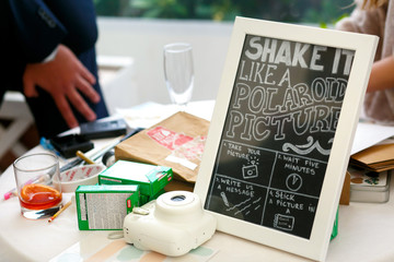 Black board with a lettering about polaroid stands on the table