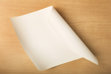 White paper with fold corner on wood background, partially rolled up