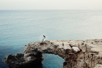 Look from afar at a beautiful couple standing on the rock by the