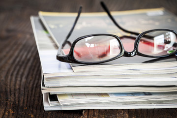 Magazines on table with eyeglasses
