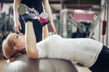 Pregnant woman doing exercises with hand handles on fitness ball in gym