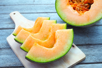 Close up of sliced rock melon on a wooden cutting board.
