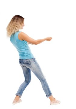 back view of standing girl pulling a rope from the top or cling to something. girl  watching. Rear view people collection.  backside view of person.  Isolated over white background. The girl in jeans