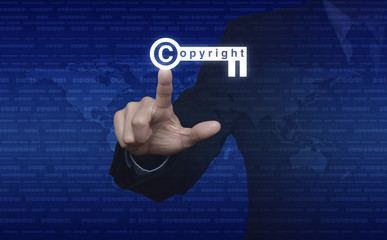 Businessman pressing copyright key icon over digital world map a