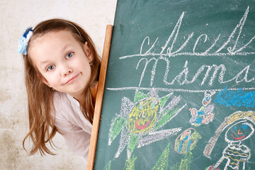 Young girl drawing and writing with chalk on the blackboard