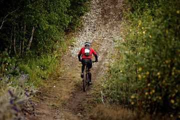 athlete mountainbiker rides a bicycle on a mountain trail. extreme sports