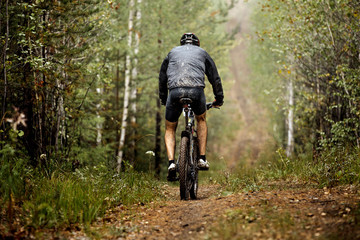 rear view of male athlete a cyclist riding along a forest trail. feet and back drops dirt