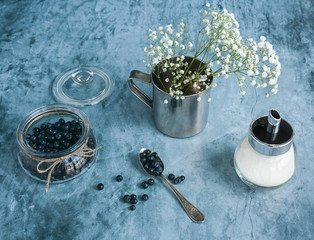 Blueberries in jar and flowers
