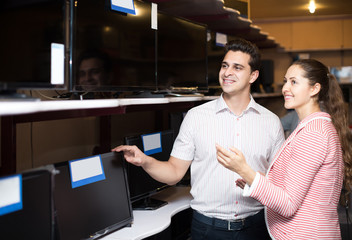 consultant helping young couple to choose PC monitor