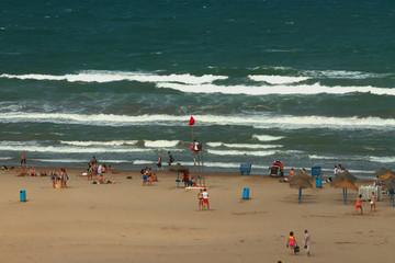 Hoisted red colors on sea beach. Valencia, Spain