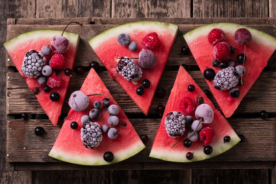 colorful tropical fruit watermelon pizza topped with berries cut into segments on a rustic wooden board