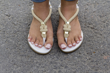 Feet girl in fashionable sandals with a beautiful pedicure on the road