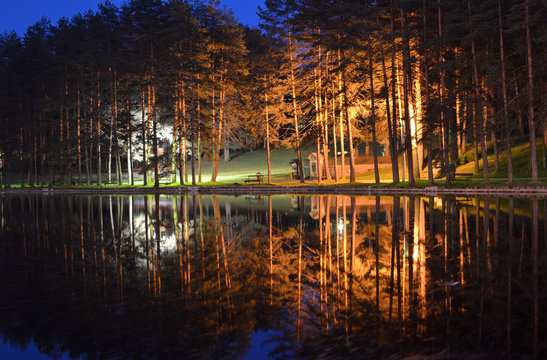 Reflection of trees and colorful lights of a promenade on the Zlatibor pond surface at dusk time