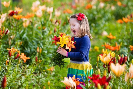 Little girl picking lilly flowers