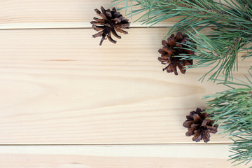 Christmas holiday decoration/ flat lay of pine branches and cones on a wooden surface top view
