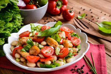Vegetable salad with white beans, fried fish pieces, red pepper, green onion and chive