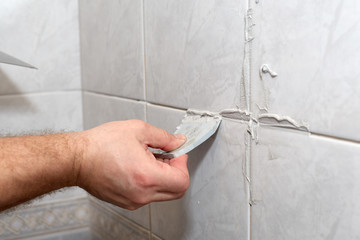 Male worker tiling a wall.