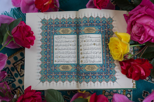 Koran with roses and rosary on white background