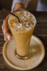 Glass of iced coffee against women's hand. Selective Focus.