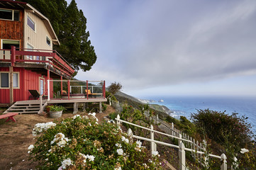 a beautiful view of a home on a cliff that overlooks the ocean