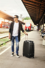 Handsome man with suitcase posing on the railway station
