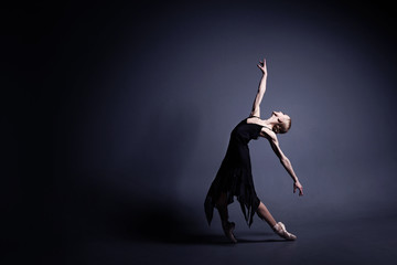 Young ballerina in a black suit is dancing in a dark studio