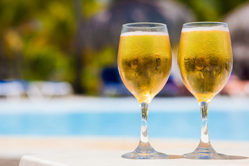 Wet glassses of beer by the pool