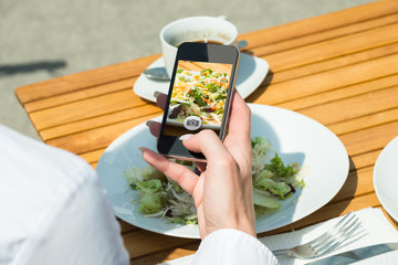 Person's Hand Taking Picture Of Food At Restaurant