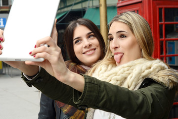 Two young girlfriends taking selfie with tablet.