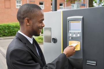 Businessman Inserting Ticket Into Parking Machine
