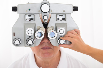 An Optometrist Adjusting Phoropter For Patient