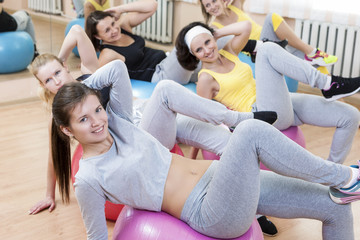 Sport Concepts. Group of Five Laughing Smiling Caucasian Females Having Abdominal Stretching Exercises