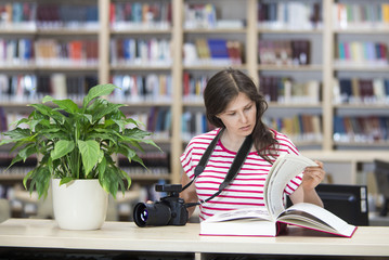 Girl with a camera in the library reading a big book