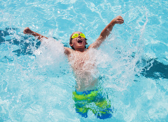 Cheerful boy in goggles in swimming pool