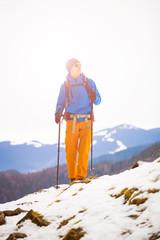 Mountain climber walks on a snowy slope.