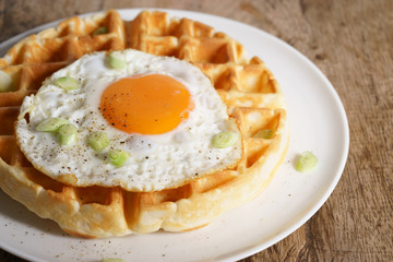 warm waffle with fried egg for breakfast.