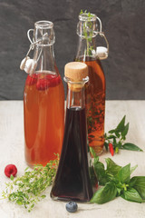 Assorted bottles of vinegar. Different kinds of vinegar in various bottles arranged with fruits, herb and hot pepper