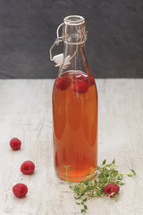 Raspberry thyme vinegar. A bottle of vinegar, a few fresh raspberries and thyme herbs on rustic background