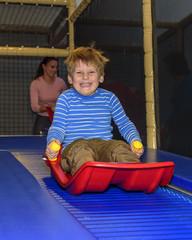 kleiner Junge hat Spass auf Rollschlittenbahn im Indoor-Freizeitpark