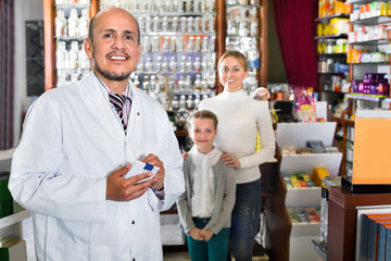 Male pharmacist working pharmaceutical store and consulting cust