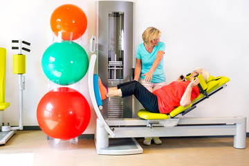Therapist with patient strengthening legs.