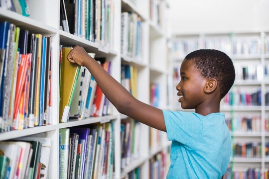 Schoolboy selecting a book from bookcase in library