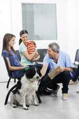 Nurse Crouching By Pets And Owners In Waiting Area