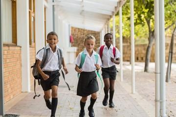 Smiling school kids running in corridor